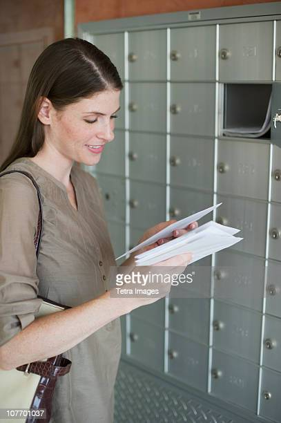 USA, New Jersey, Woman checking post next to mailboxes