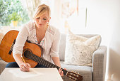 USA, New Jersey, Woman sitting on sofa with acoustic guitar and writing