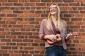 USA, New Jersey, Woman standing against brick wall and playing ukulele