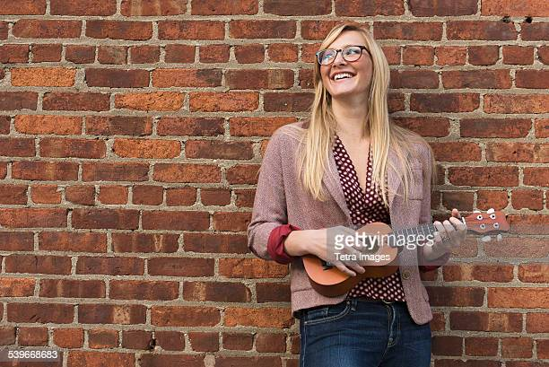 USA, New Jersey, Woman standing against brick wall and playing ukulele