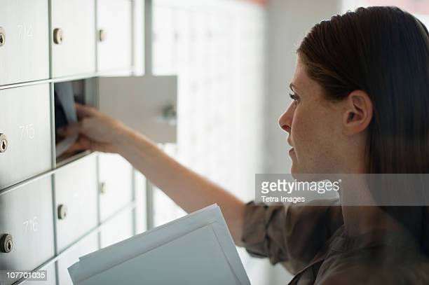 USA, New Jersey, Woman taking letters from mailbox