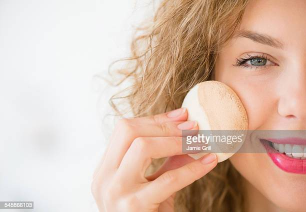 USA, New Jersey, Young woman applying make up foundation