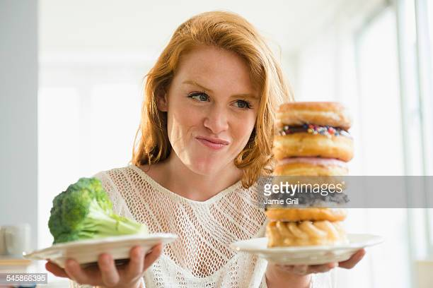 USA, New Jersey, Young woman holding plate with donut and with broccoli