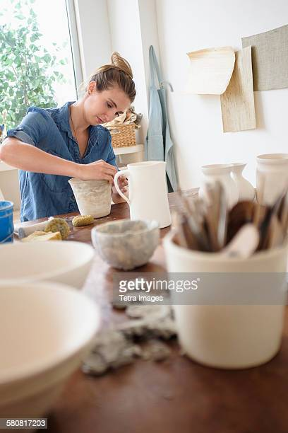 USA, New Jersey, Young woman making pottery in studio