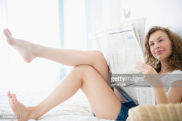 USA, New Jersey, Young woman sitting on bed and reading newspaper