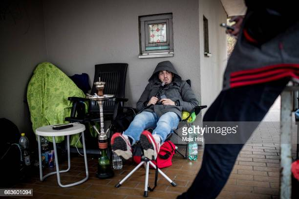 New KAWS x Air Jordan IV sneakers buyers smoke shisha as they wait near the 'Overkill' sneakers store on March 30 2017 in Berlin Germany Several...