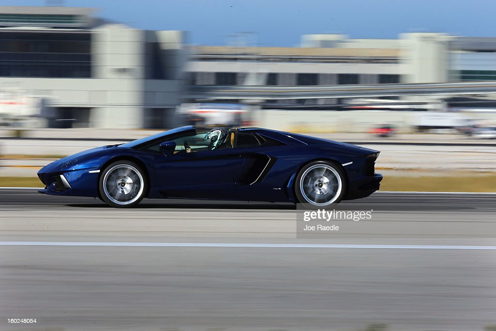 A new Lamborghini Aventador LP700-4 Roadster is seen as it is driven along the south runway at the Miami International Airporton January 28, 2013 in Miami, Florida. The world wide unveiling of the new luxury super sports cars took place at the airport.