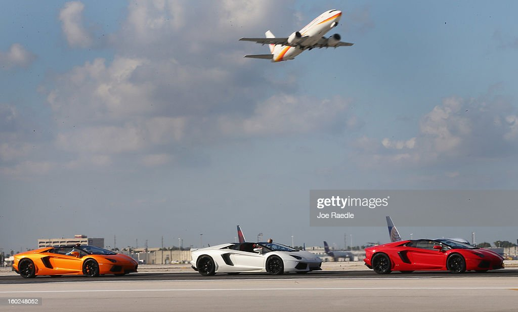 New Lamborghini Aventador LP700-4 Roadsters are seen as they are driven along the south runway at the Miami International Airporton January 28, 2013 in Miami, Florida. The world wide unveiling of the new luxury super sports cars took place at the airport.