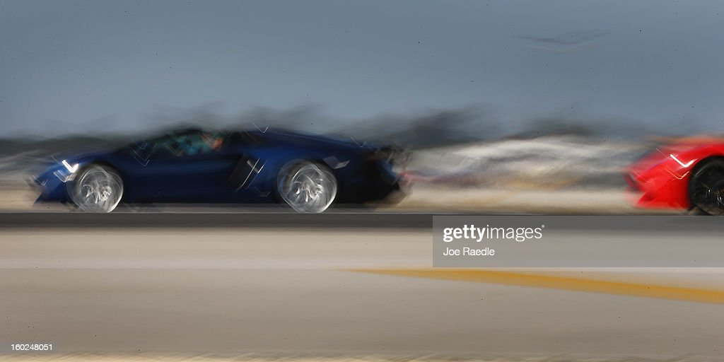 New Lamborghini Aventador LP700-4 Roadsters are seen using a slow shutter speed as they are driven along the south runway at the Miami International Airporton January 28, 2013 in Miami, Florida. The world wide unveiling of the new luxury super sports cars took place at the airport.