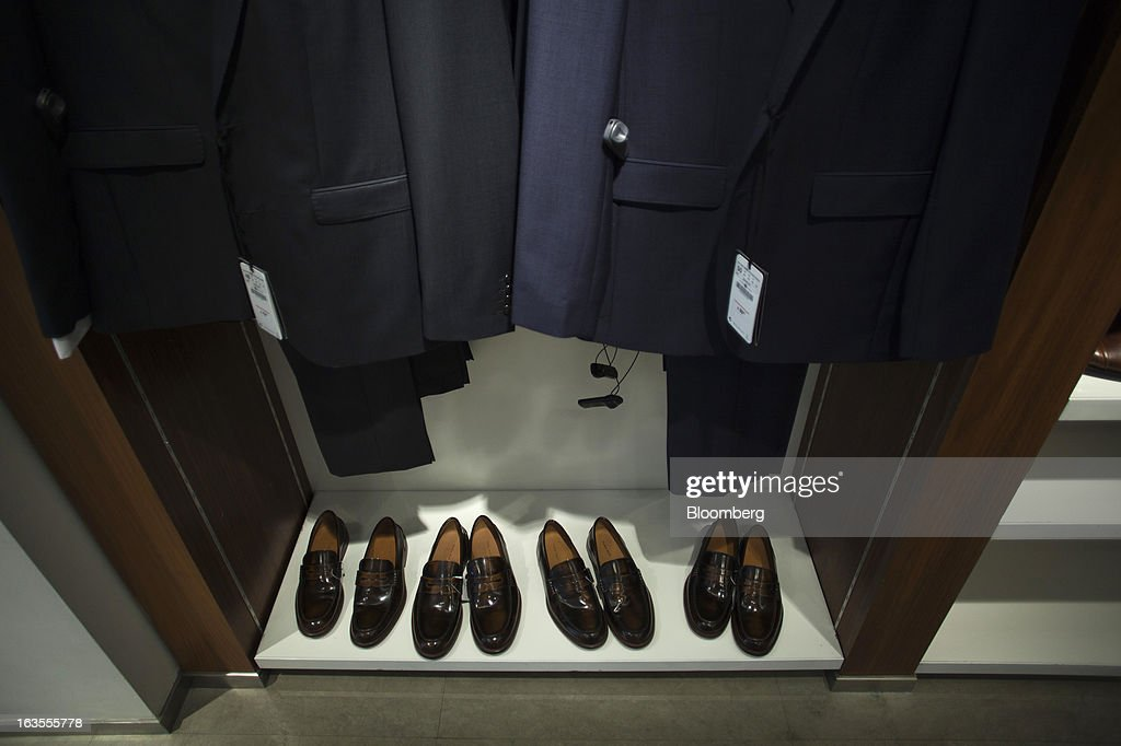 New loafers sit beneath a display of men's suits inside a Zara fashion store, operated by Inditex SA, in Madrid, Spain, on Tuesday, March 12, 2013. Europe's richest man, Amancio Ortega, the 76-year-old founder of Inditex SA, the world's biggest clothing retailer and owner of the Zara clothing chain, is No. 3 on Standard & Poor's 500 Index with a net worth of $57.4 billion, $4.9 billion ahead of Warren Buffett, 82. Photographer: Angel Navarrete/Bloomberg via Getty Images
