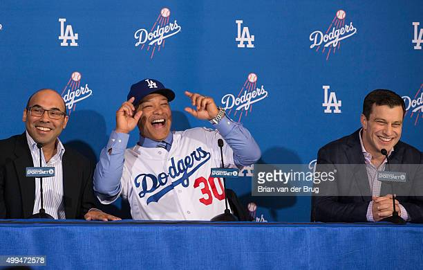 New Los Angeles Dodgers manager Dave Roberts center shares a laugh on stage with General Manager Farhan Zaidi left and President of Baseball...