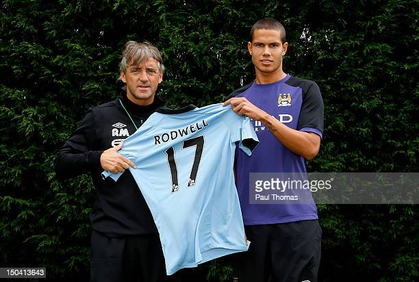 New Manchester City player Jack Rodwell and manager manager Roberto Mancini pose for a photograph at the MCFC Carrington Training Complex on August...