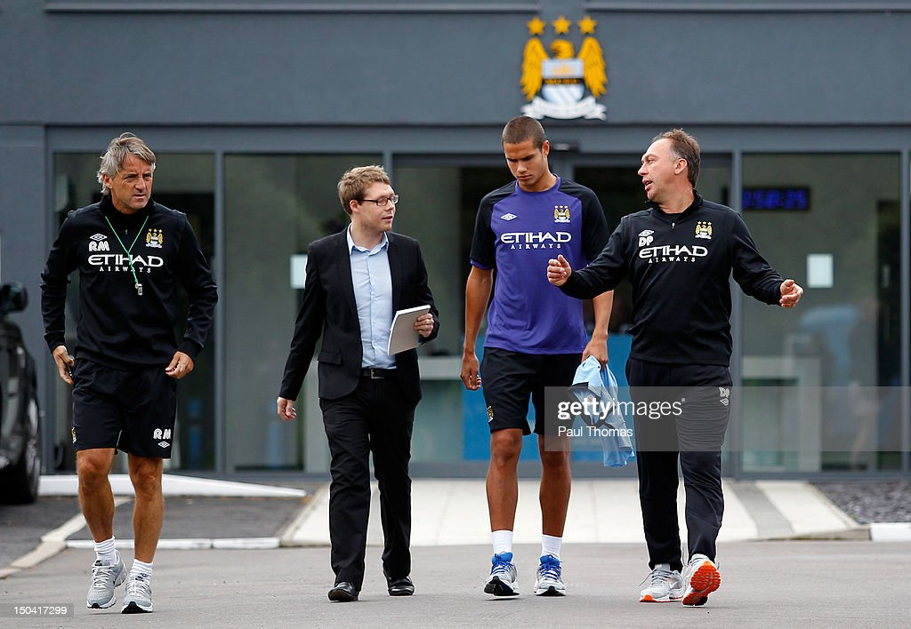 New Manchester City player Jack Rodwell (2nd R) arrives ahead of the press conference with manager Roberto Mancini (L) and first team coach David Platt (R) at the MCFC Carrington Training Complex on August 17, 2012 in Manchester, England.