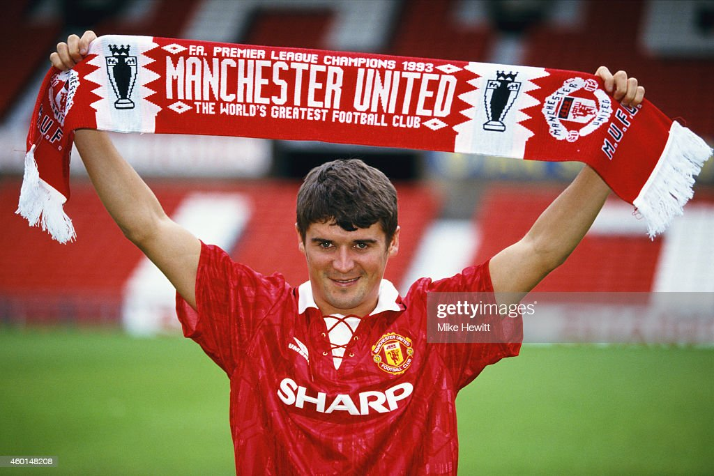 New Manchester United signing Roy Keane poses with a club scarf at Old Trafford after signing from Nottingham Forest ahead of the 1993/94 season