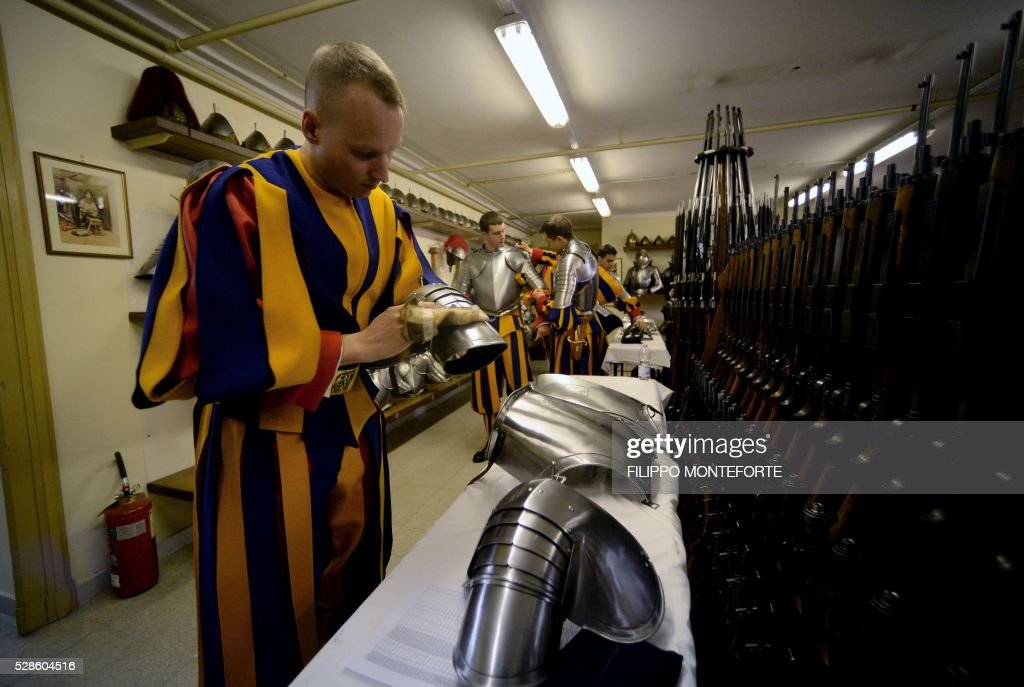 A new member of the Vatican Swiss Guard polishes his body armour prior to a swearing-in ceremony in Vatican City, on May 6, 2016. The annual swearing in ceremony for the new papal Swiss guards takes place on May 6, commemorating the 147 who died defending Pope Clement VII on the same day in 1527. / AFP / FILIPPO