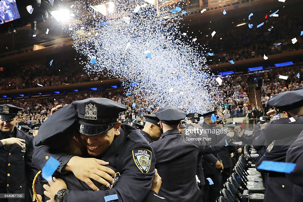 New members of New York's police department's graduating class celebrate in Madison Square Garden after a swearing in ceremony on July 1, 2016 in New York City. The New York City Police Department's (NYPD) current uniformed strength is approximately 34,500.