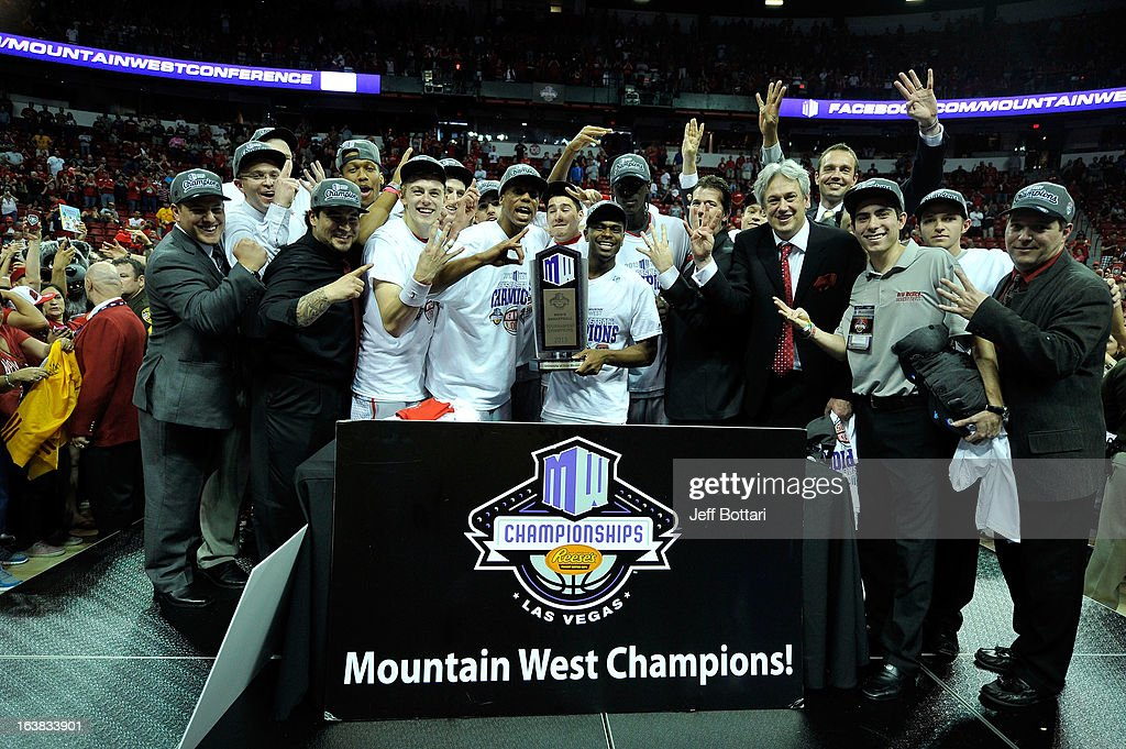 New Mexico Lobos players and coaches celebrate with the trophy after their 63-56 win over the UNLV Rebels in the championship game of the Reese's Mountain West Conference Basketball tournament at the Thomas & Mack Center on March 16, 2013 in Las Vegas, Nevada.