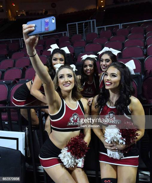 New Mexico State Aggies cheerleaders pose for a selfie before the championship game of the Western Athletic Conference Basketball tournament against...