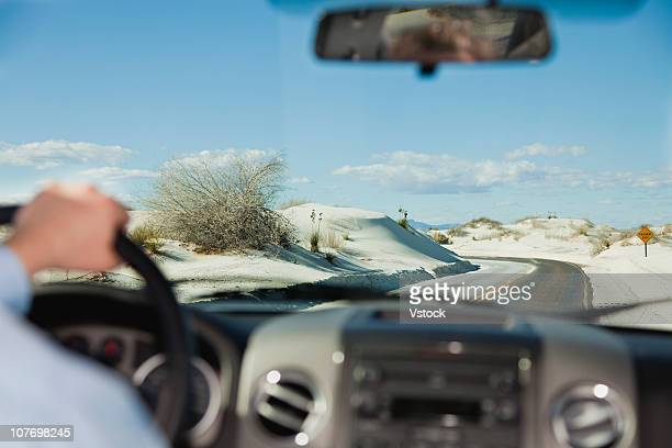 USA, New Mexico, White Sands National Monument, Businessman using binoculars on rock
