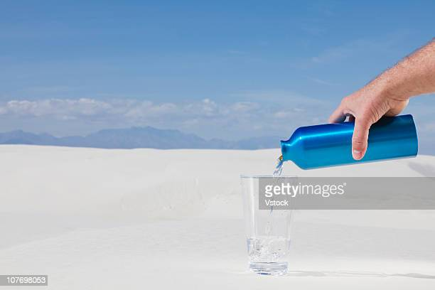 USA, New Mexico, White Sands National Monument, Mans hand pouring water in desert
