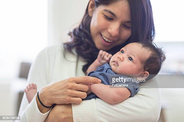 New mother smiling and holding newborn baby at home