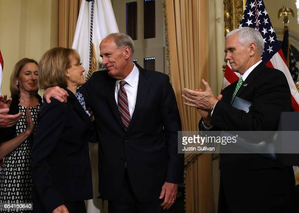 New National Intelligence Director Dan Coats hugs his wife Marsha Coats as US Vice President Mike Pence applauds at Coats' swearingin ceremony at the...