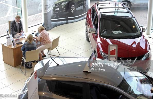 New Nissan automobiles produced by Nissan Motor Co stand displayed for sale as a salesman left talks to customers at Toomey Motor Group's car...
