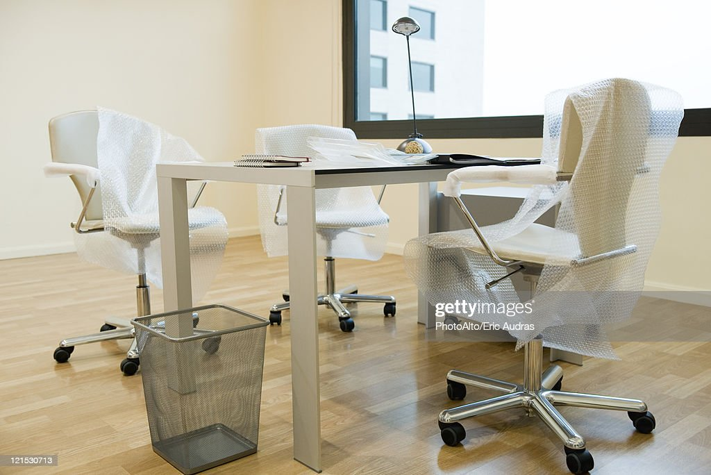 New office chairs covered in bubble wrap : Stock Photo
