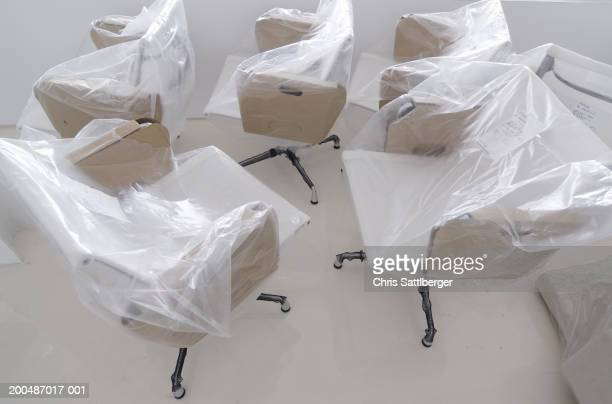 New office chairs covered in protective plastic sheets