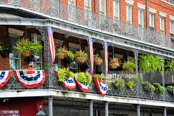 New Orleans balcony, wrought iron railing, flag banners, French Quarter