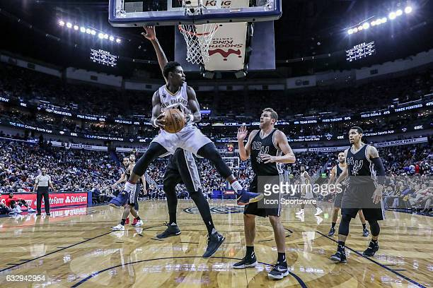 New Orleans Pelicans guard Jrue Holiday looks to pass the ball against San Antonio Spurs forward David Lee during the game between the New Orleans...