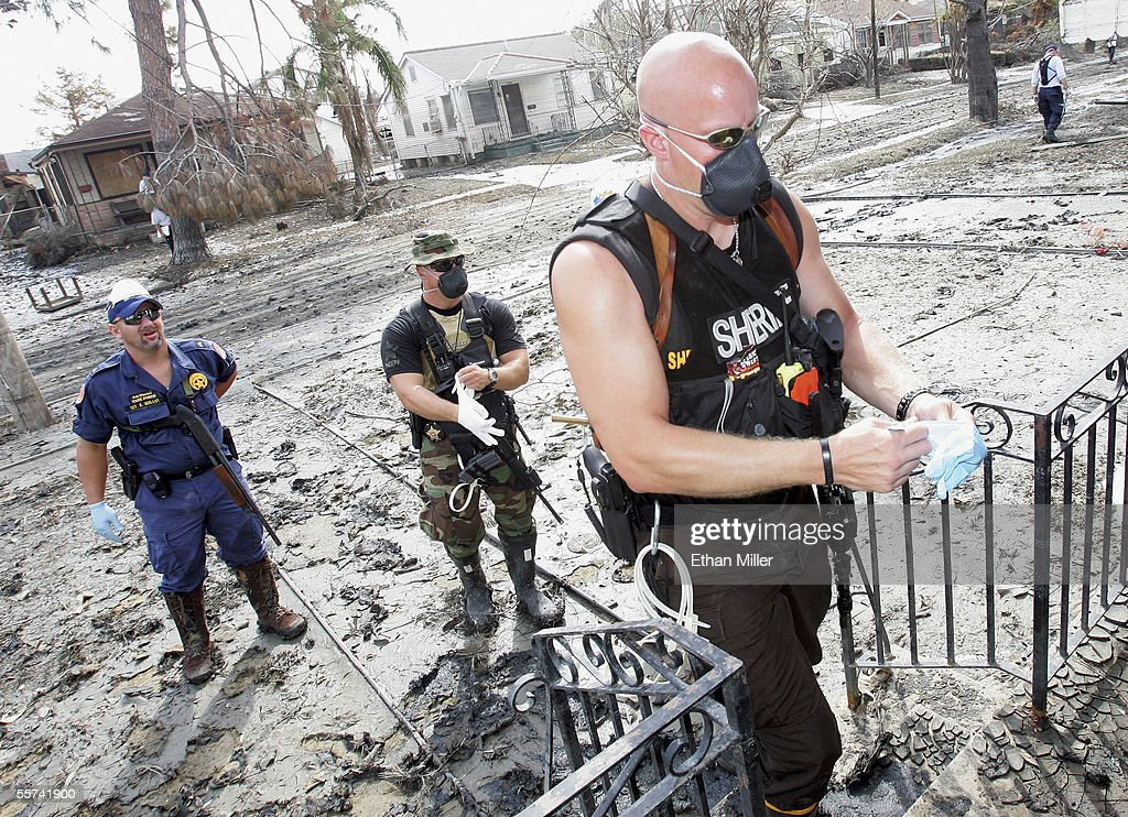 New Orleans Police Sgt. Kevin Guillot, Deputy Mike Thommes and Deputy Donald Rindal, both from the Ramsey County Sheriff's Department in St. Paul, Minnesota, prepare to enter a home to collect guns found by members of the Pennsylvania Task Force-1 Urban Search & Rescue searching for victims of Hurricane Katrina on Wildair Drive in the Gentilly Terrace District September 22, 2005 in New Orleans, Louisiana. The body count from Hurricane Katrina has risen to over 1,000, although the search may be hampered by the threat from Hurricane Rita.