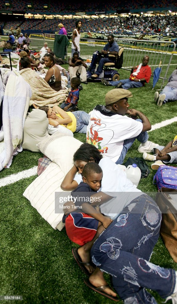 New Orleans residents sit in the Superdome, which is being used as an emergency shelter, before the arrival of Hurricane Katrina August 28, 2005 in New Orleans, Louisiana. Hurricane Katrina has sustained winds of 175 mph and is expected to make landfall in the Gulf Coast as early as August 29. Katrina killed at least seven when it moved through Miami-Dade County in Florida.