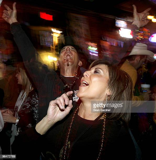 New Orleans Saints fans dance to the beat of the famous song 'When the Saints Go Marching In' at a bar on Bourbon Street on February 6 2010 in New...