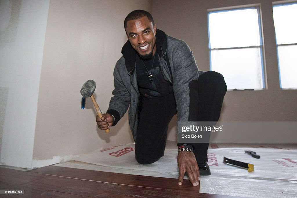 NFL New Orleans Saints player Darren Sharper helps to put down the floor as NFL New Orleans Saints Players Darren Sharper and Roman Harper team up...