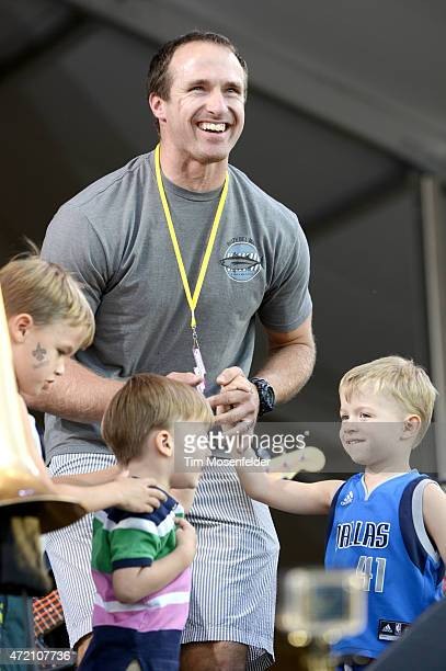 New Orleans Saints Quarterback Drew Brees and children join Trombone Shorty onstage during the 2015 New Orleans Jazz Heritage Festival at Fair...