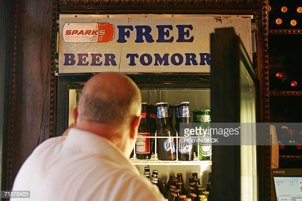A humorous sign is posted on a refrigerator as a bartender reaches for a beer at a restaurant in the French Quarter of New Orleans 10 July 2006...
