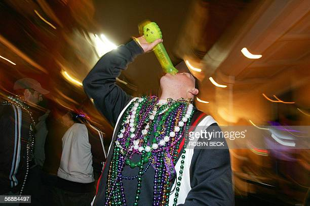 A reveler downs a 'hand grenade' alcohol drink while partying on Bourbon Street in the French Quarter of New Orleans at the start Mardi Gras 18...
