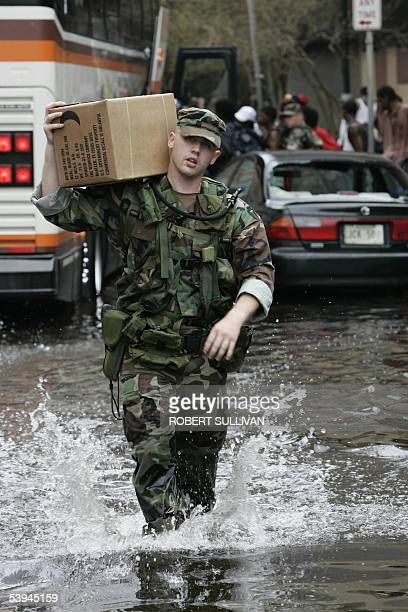 A US soldier carries a box of MREs to be distributed to people leaving the Superdome in New Orleans 01 September 2005 Survivors of Hurricane Katrina...