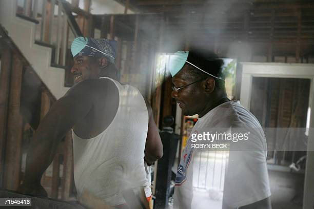 Don Woods and his brotherinlaw Fredrick Smith work together to gut Wood's flooddamaged home in the Lower Ninth Ward of New Orleans 11 July 2006 With...