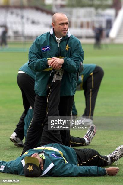 New Pakistan coach Richard Pybus helps Wasim Akram with his warmup routine during a training session at Trent Bridge Nottingham Pakistan will play...