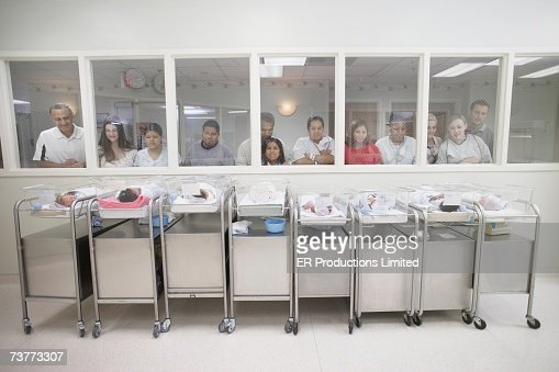 New parents watching babies in hospital nursery : Stock Photo