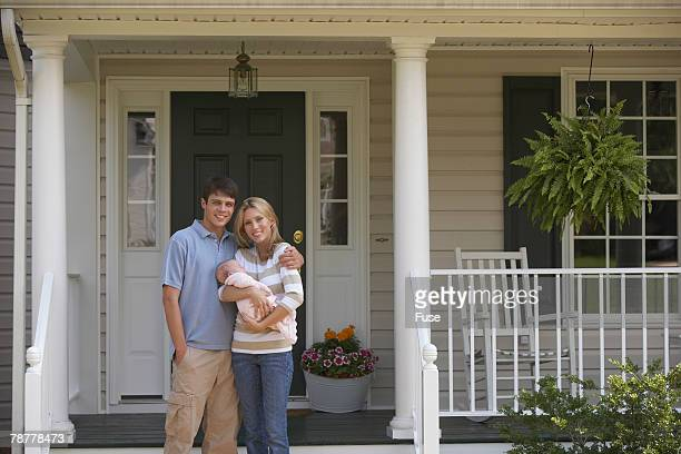 New Parents with Baby in Front of House
