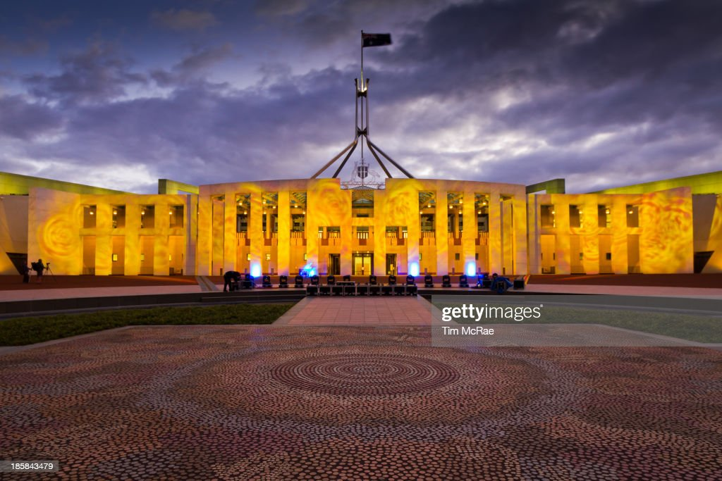 CONTENT] New Parliament House in Canberra ACT Australia Lit up during the Enlighten project Aboriginal mosaic in the forground Early evening light...