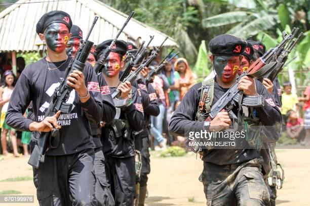 New Peoples Army guerillas the armed wing of the Maoist rebels march during the turnover ceremony of captured government soldiers to officials and...
