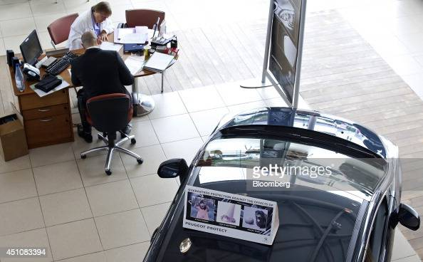 A new Peugeot automobile produced by PSA Peugeot Citroen stands behind a salesman bottom as he helps a customer complete paperwork inside Toomey...