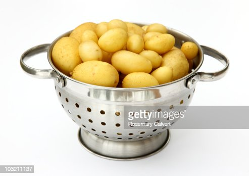 New potatoes in colander scrubbed ready to cook. : Foto de stock