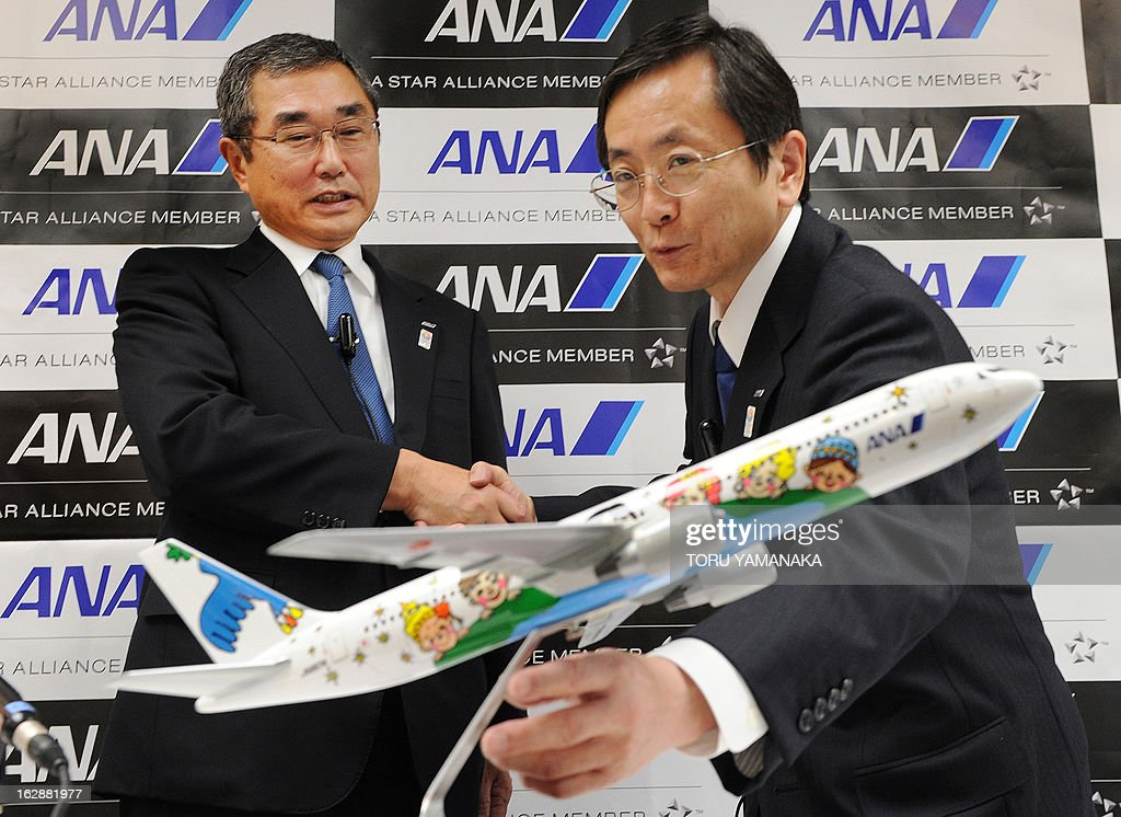 New President and CEO of ANA Group Osamu Shinobe (R) stretches for a miniature of Boeging 767-300 as he shakes hands with new President and CEO of ANA Holdings Shinichiro Ito (L) during a press conference at their headquarters in Tokyo on March 1, 2013. Japan's airlines announced on March 1 a series of management changes reflecting its move to a holding company structure from April 1. AFP PHOTO / Toru YAMANAKA