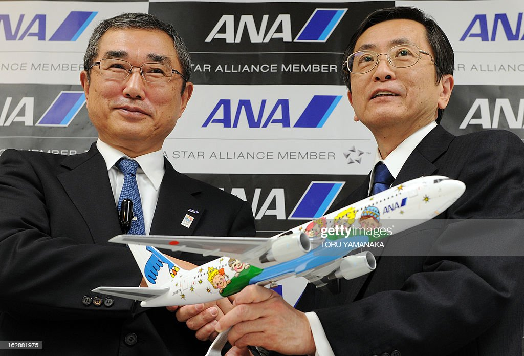 New President and CEO of ANA Holdings Shinichiro Ito (L) and new President and CEO of ANA Group Osamu Shinobe (R) hold a miniature Boeing 767-300 during a press conference at their headquarters in Tokyo on March 1, 2013. Japan's airlines announced on March 1 a series of management changes reflecting its move to a holding company structure from April 1. AFP PHOTO / Toru YAMANAKA