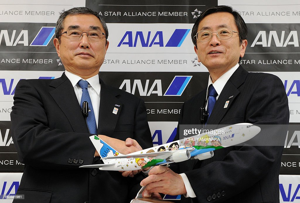New President and CEO of ANA Holdings Shinichiro Ito (L) and new President and CEO of ANA Group Osamu Shinobe (R) hold a miniature of Boeing 767-300 during a press conference at their headquarters in Tokyo on March 1, 2013. Japan's airlines announced on March 1 a series of management changes reflecting its move to a holding company structure from April 1. AFP PHOTO / Toru YAMANAKA